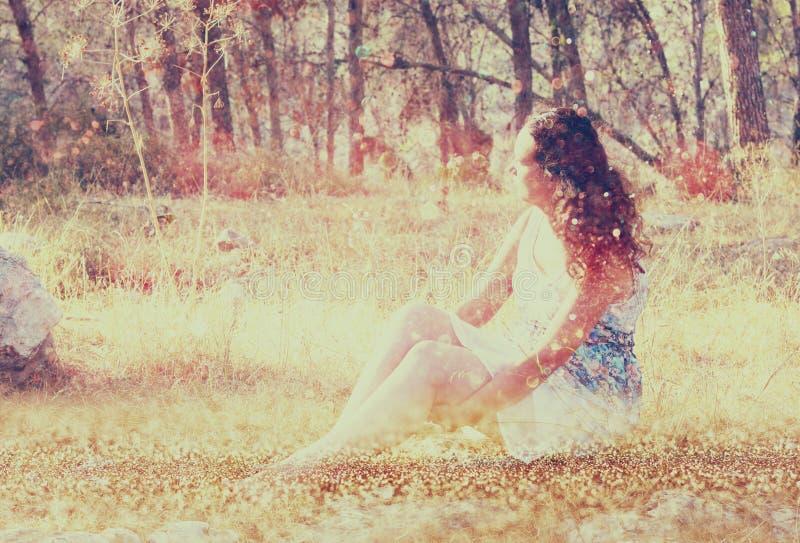Fondo vago surreale della giovane donna che si siede sulla pietra nel concetto astratto e vago della foresta l'immagine è struttu immagini stock