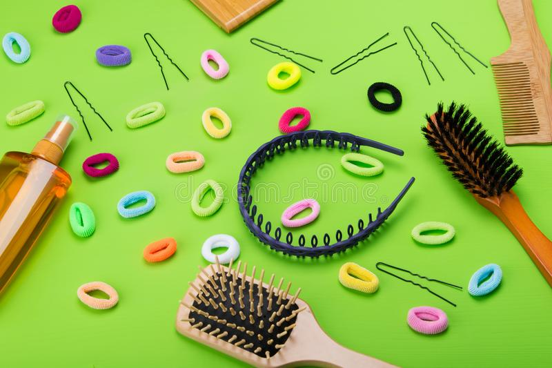 fondo verde chiaro, oggetti sparsi per creare la banda elastica, dell'acconciatura dei colori differenti e un pettine e uno spruz fotografie stock