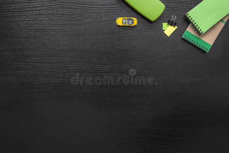 Fondo verde, giallo, nero di affari della scrivania con il Post-it, automobile, clip del raccoglitore, blocco note e spettacolo-c immagine stock libera da diritti