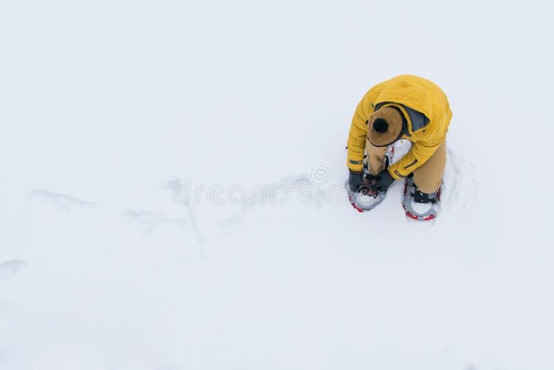 fondo, vista superiore, uomo nella neve in un rivestimento giallo, racchette da neve d'uso da sopravvivere a e passare sopra immagini stock