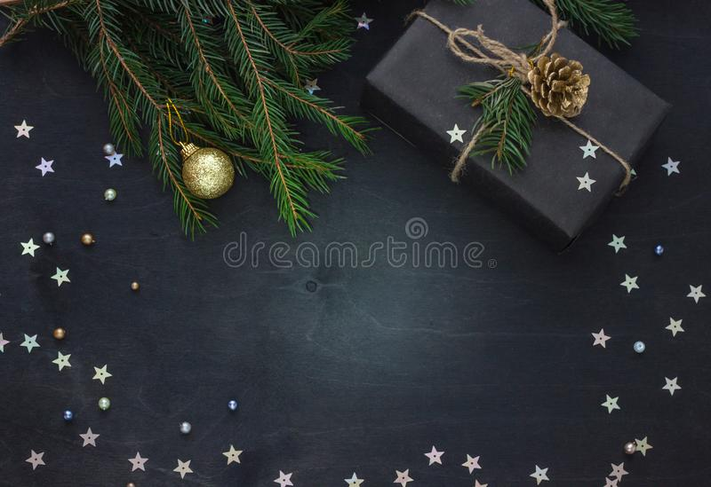 Fondo y marco elegantes del negro de la Navidad, del Año Nuevo con una rama del abeto y de un regalo imágenes de archivo libres de regalías