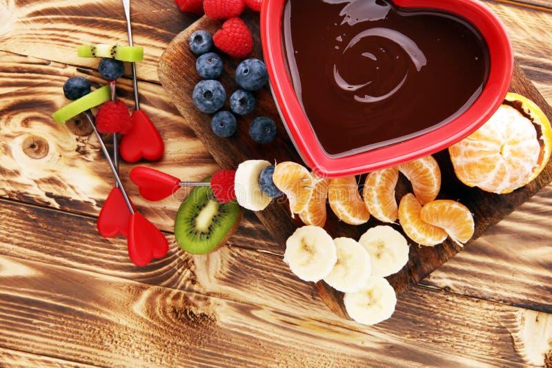 'fondue' de chocolate con el surtido de las frutas en tabla de cortar de madera foto de archivo libre de regalías