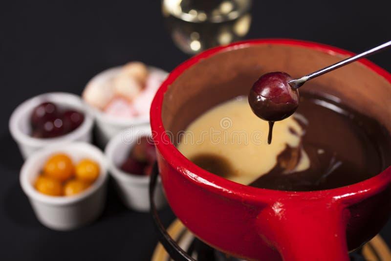 'fondue' de chocolate con la uva en el pote rojo imagen de archivo libre de regalías