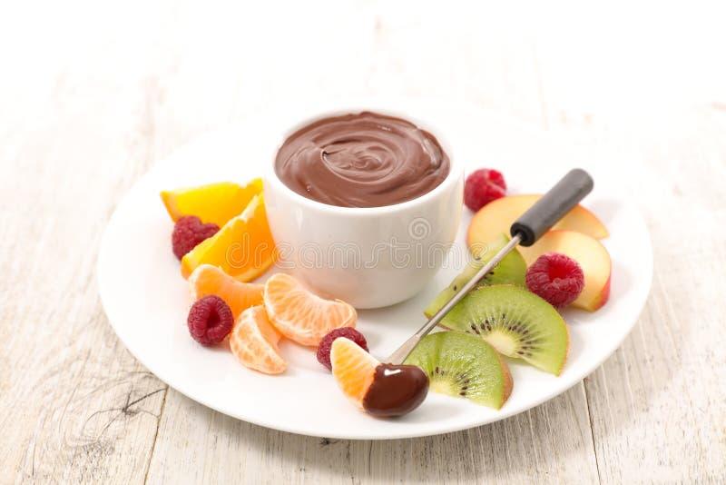 'fondue' de chocolate con las frutas foto de archivo