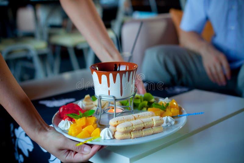 'fondue' de chocolate con las frutas en pote azul imagenes de archivo