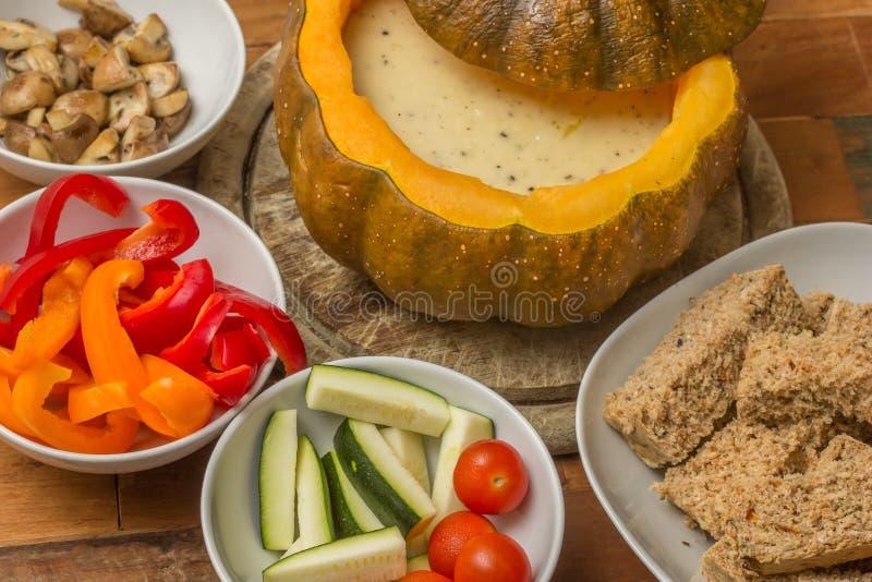 Fondue de queijo em uma abóbora roasted com pão e vegetais fotografia de stock