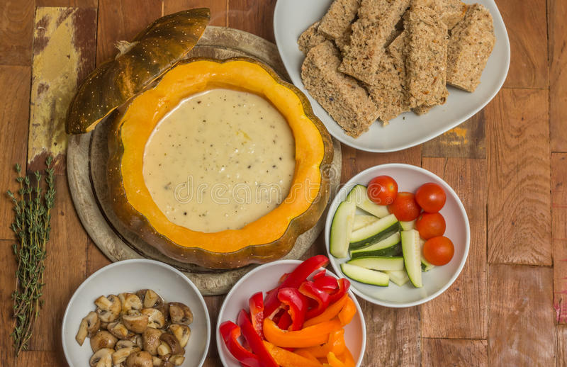 Fondue de queijo em uma abóbora roasted com pão e vegetais imagens de stock