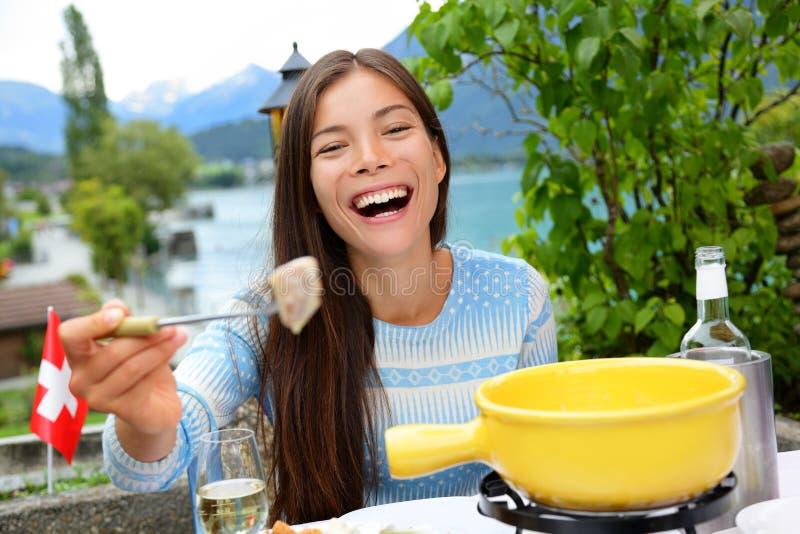 Fondue de queijo suíço - riso comer da mulher imagens de stock royalty free