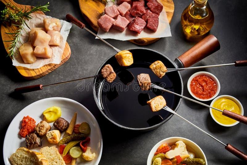 Fondue delicioso do inverno com carne sortido fotografia de stock royalty free
