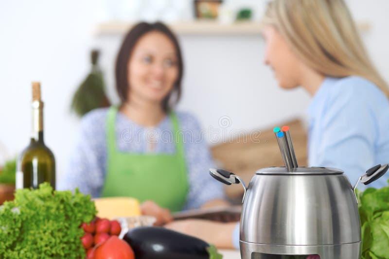 Fondue w garnku przy tłem przyjaciele gotuje wpólnie, zakończenie Kuchenni wnętrza i cookware zdjęcia stock