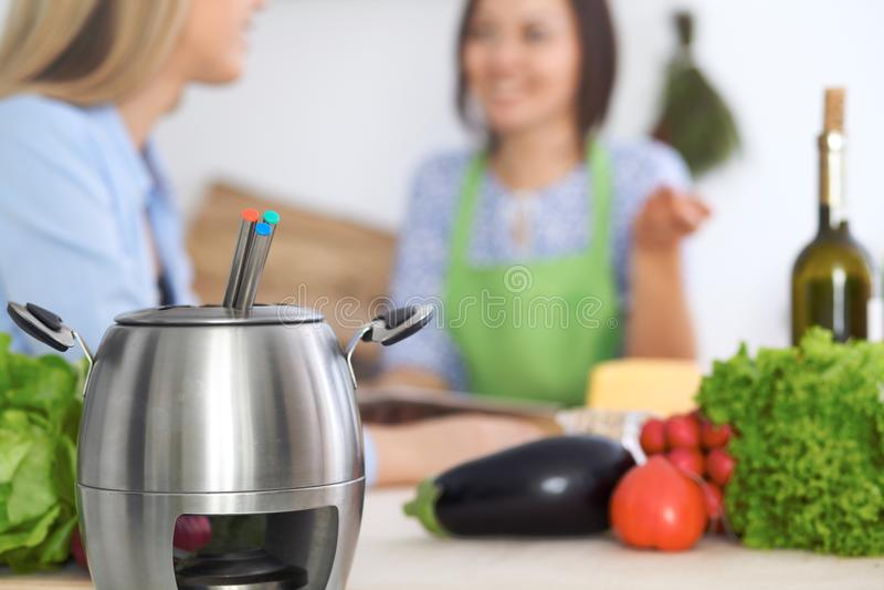 Fondue w garnku przy tłem przyjaciele gotuje wpólnie, zakończenie Kuchenni wnętrza i cookware zdjęcie royalty free