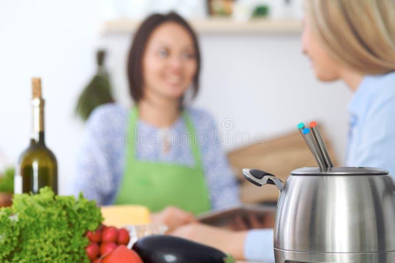 Fondue w garnku przy tłem przyjaciele gotuje wpólnie, zakończenie Kuchenni wnętrza i cookware fotografia royalty free