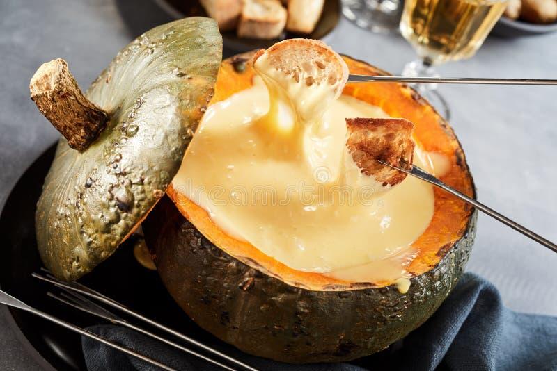 Fonduta di formaggio cremosa in una zucca o in una zucca fotografia stock
