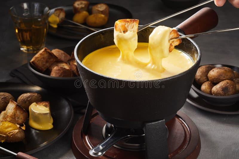 Fonduta di formaggio fusa deliziosa con la immersione delle forcelle fotografie stock libere da diritti