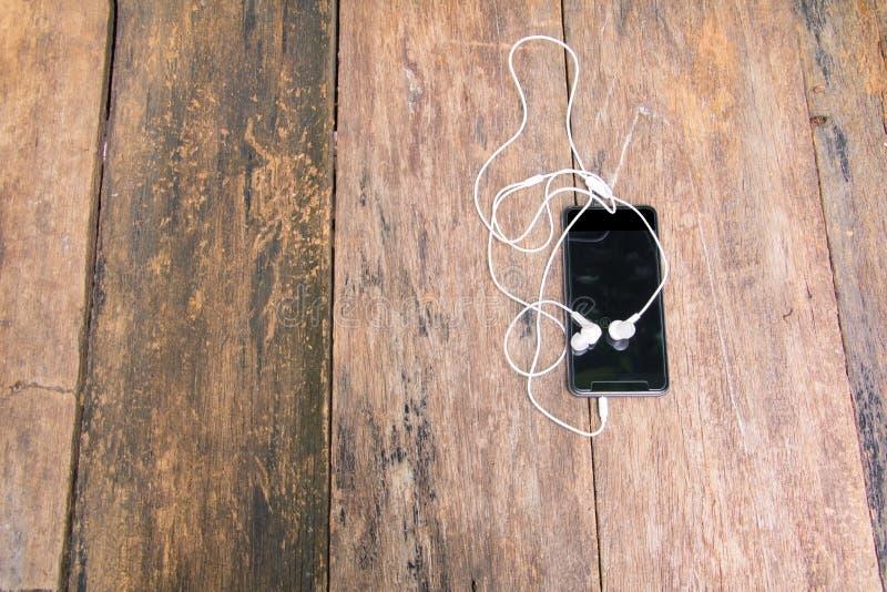 Fone de ouvido branco no telefone celular com fundo do vintage da tabela e espaço de madeira velhos da cópia Vista superior fotos de stock
