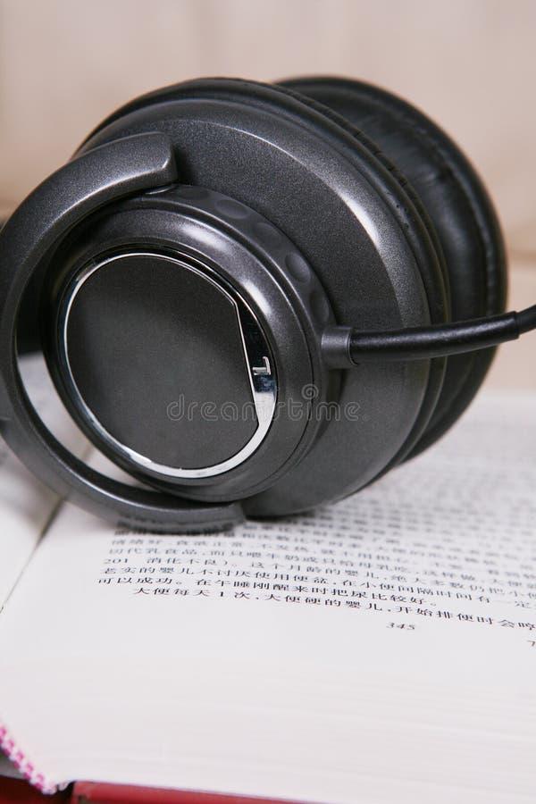 Fone de ouvido com livro imagem de stock royalty free