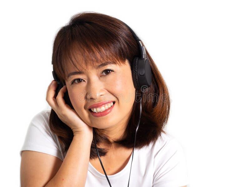 Fone de ouvido de escuta asiático da mulher adulta Momento da felicidade com música fotos de stock royalty free