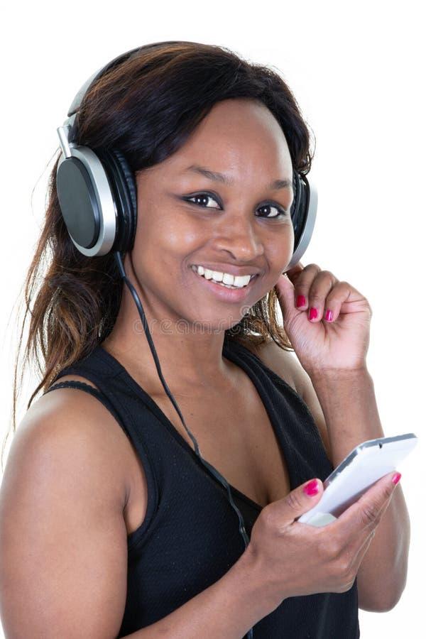 Fones de ouvido africano americano da mulher que escuta a música de seu telefone imagens de stock