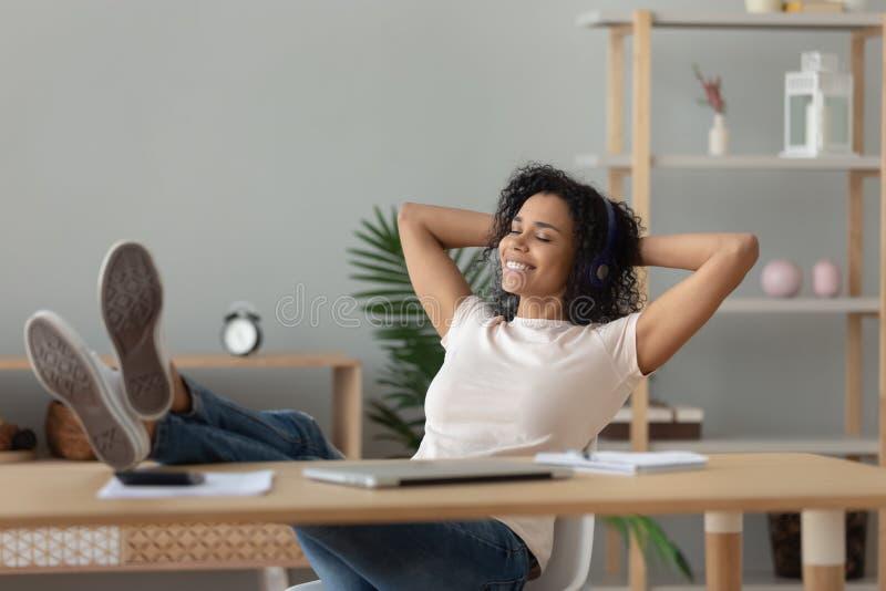 Fones de ouvido africanos relaxados do desgaste de mulher que escutam a música na mesa fotos de stock royalty free