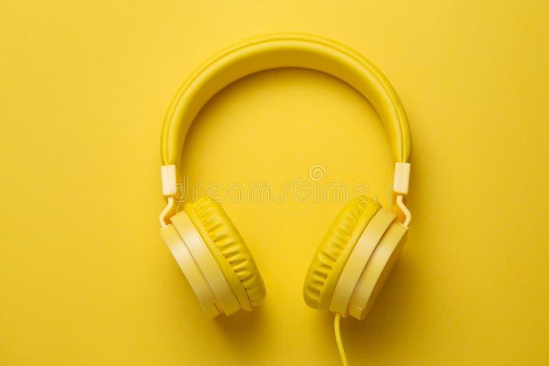 Fones de ouvido amarelos no fundo amarelo Conceito da música imagens de stock royalty free