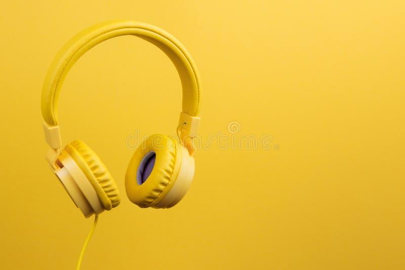 Fones de ouvido amarelos no fundo amarelo Conceito da música foto de stock royalty free