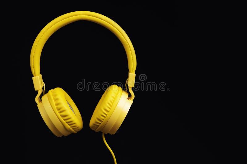 Fones de ouvido amarelos no fundo do preto escuro Conceito da música fotografia de stock royalty free