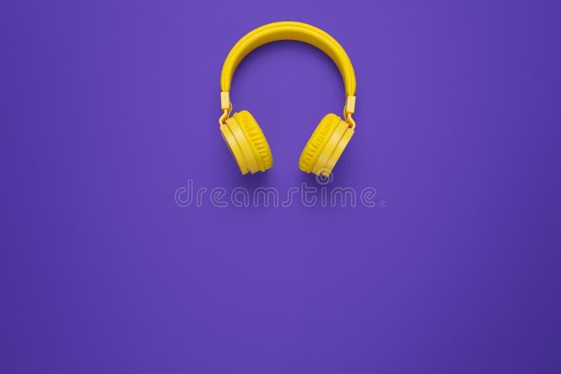 Fones de ouvido amarelos no fundo roxo Conceito da música fotografia de stock