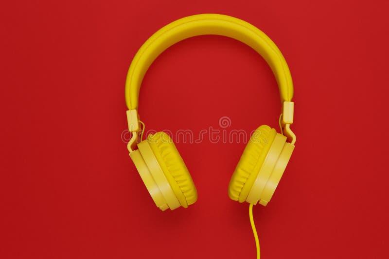 Fones de ouvido amarelos no fundo vermelho Conceito da música fotografia de stock