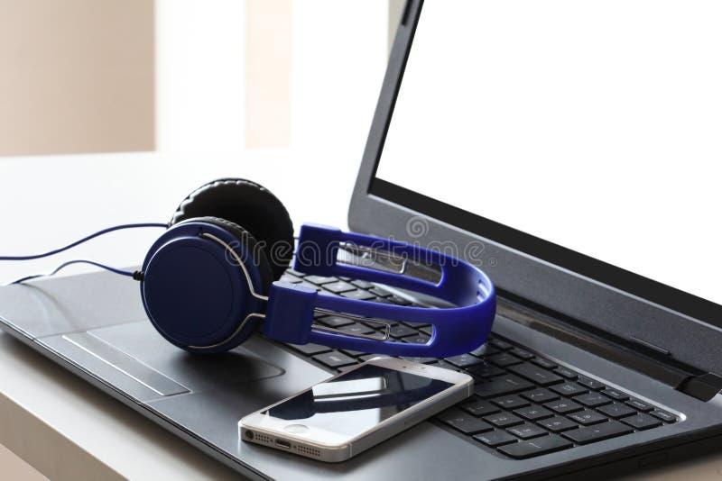 Fones de ouvido azuis e um resto esperto do telefone em um laptop com o trajeto de grampeamento no espaço da tela e da cópia do P fotografia de stock
