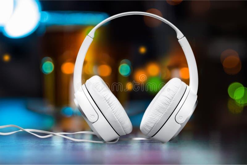 Fones de ouvido brancos modernos no fundo colorido imagens de stock royalty free