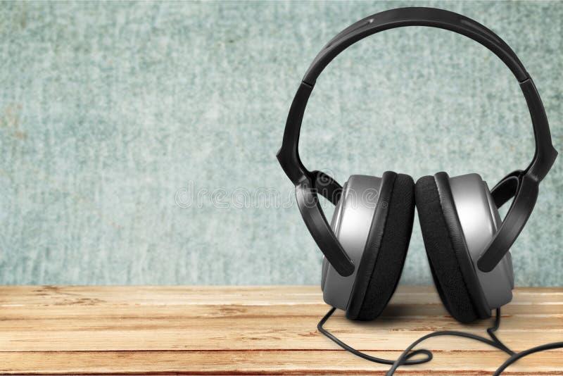 Fones de ouvido brancos modernos no fundo de madeira fotografia de stock royalty free