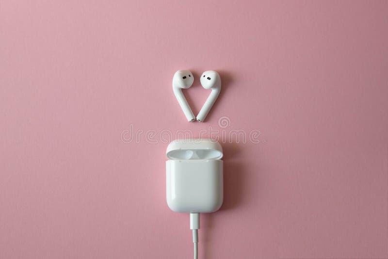 Fones de ouvido brancos sem fio no fundo cor-de-rosa Airpods fones de ouvido brancos sem fio com o carregador conectado Copie o e imagem de stock