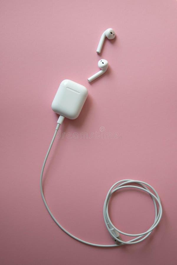 Fones de ouvido brancos sem fio no fundo cor-de-rosa Airpods fones de ouvido sem fio brancos com um carregador conectado a um cab imagens de stock royalty free