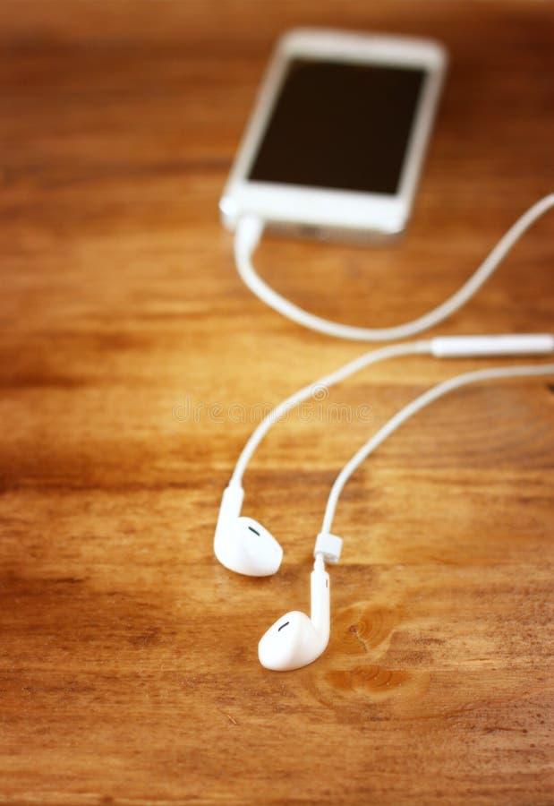 Fones de ouvido brancos unidos ao smartphone foco seletivo em fones de ouvido imagem de stock royalty free
