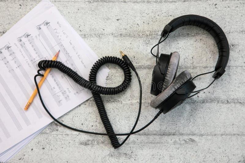 Fones de ouvido com cabo e folha de música imagem de stock royalty free