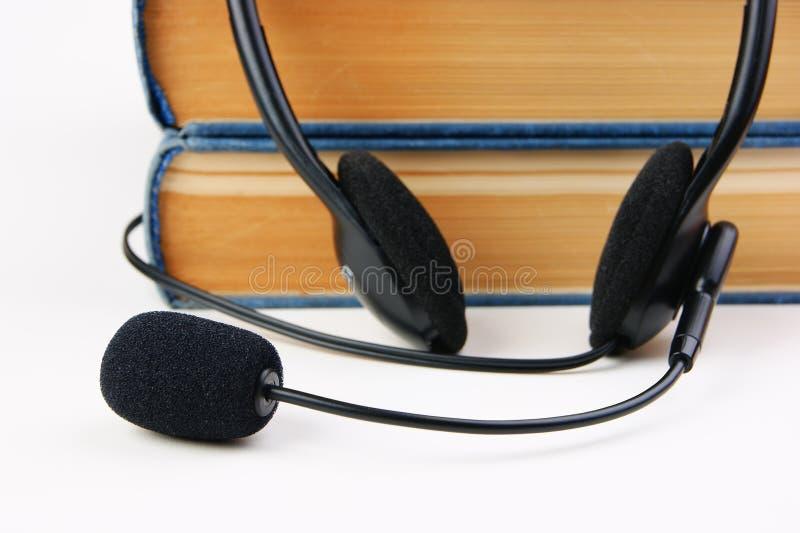 Fones de ouvido com um microfone e uma pilha de livros no backg branco imagem de stock royalty free