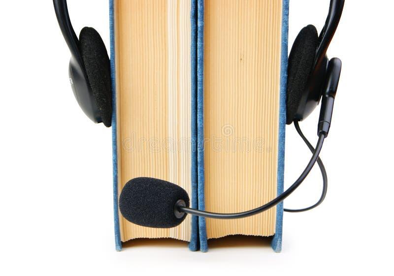 Fones de ouvido com um microfone e uma pilha de livros no fundo branco fotos de stock