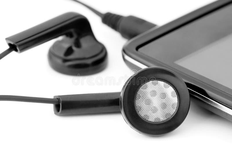 Fones de ouvido conectados a um telefone celular foto de stock royalty free