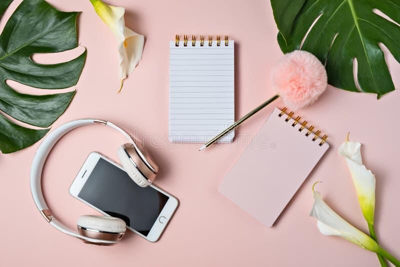 Fones de ouvido cor-de-rosa, telefone, bloco de notas vazio e pena no fundo cor-de-rosa com folha do monstera, vista superior fotografia de stock royalty free