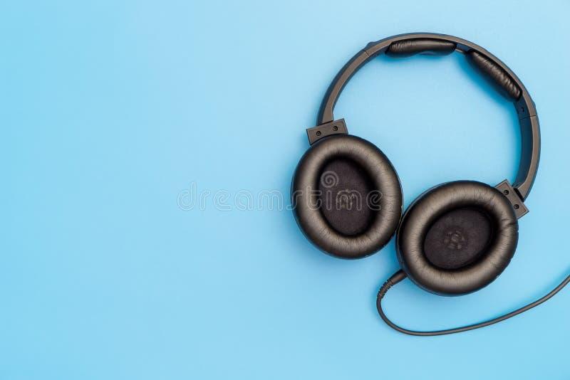 Fones de ouvido de couro preto no azul para o conceito da música imagem de stock royalty free