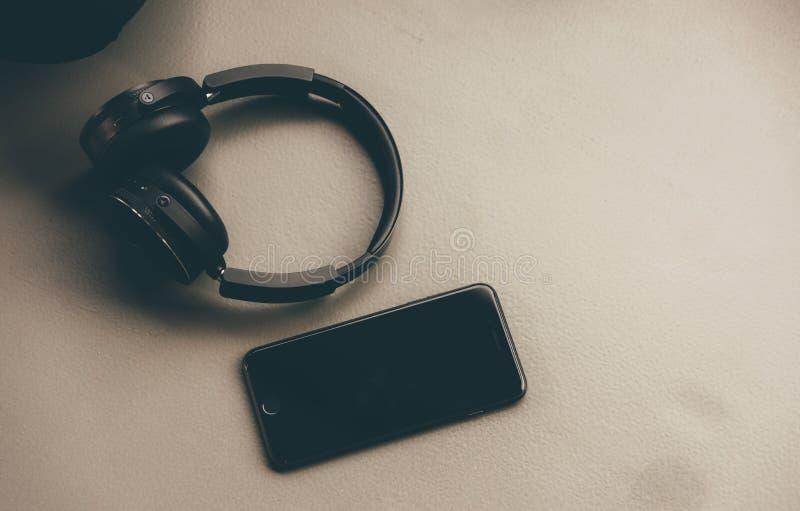 Fones de ouvido da música e telefone esperto no assoalho de borracha foto de stock