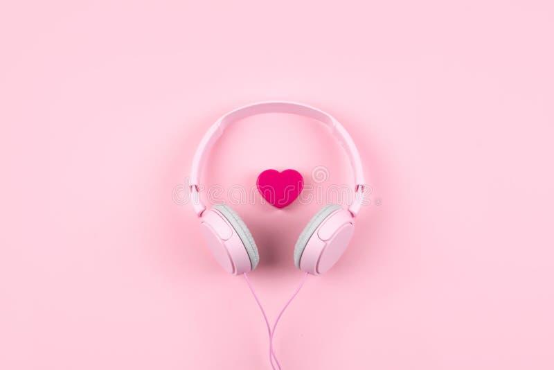 Fones de ouvido e coração cor-de-rosa no fundo cor-de-rosa Conceito mínimo da música Vista superior Configuração lisa imagem de stock royalty free