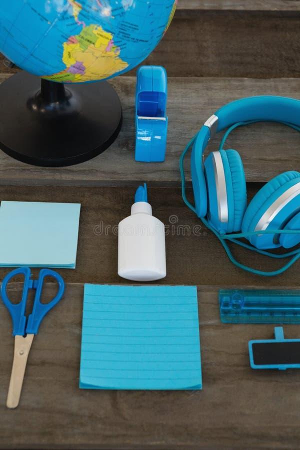 Fones de ouvido e globo com vários artigos de papelaria na superfície de madeira imagens de stock
