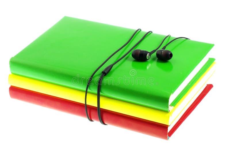 Fones de ouvido e pilha de livros coloridos em um fundo branco fotos de stock royalty free