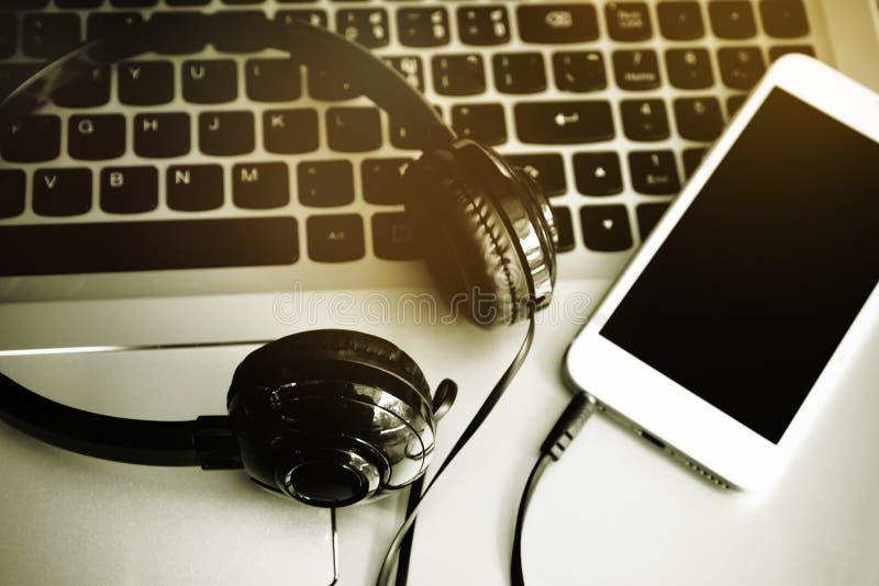 Fones de ouvido estereofônicos, telefone celular e o teclado de um computador, música em linha, música da transferência no móbil fotografia de stock royalty free