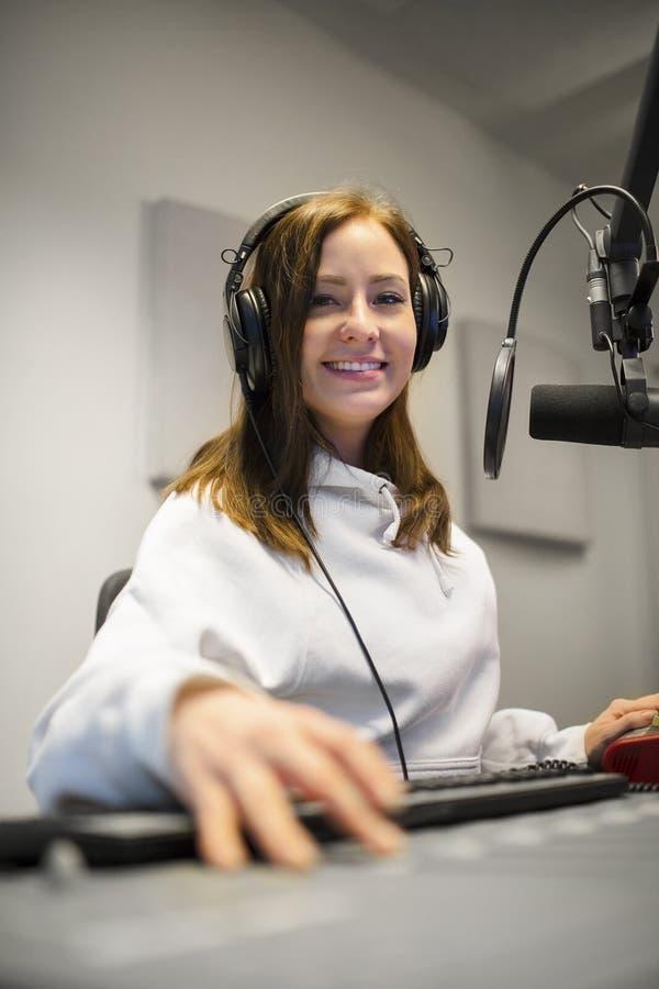 Fones de ouvido fêmeas de Smiling While Wearing do jóquei no estúdio de rádio fotografia de stock