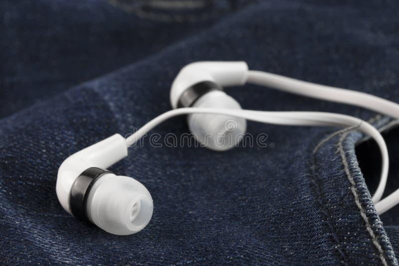 Fones de ouvido nas calças de brim velhas do bolso fotos de stock royalty free