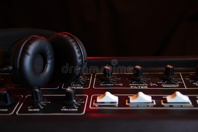 Fones de ouvido no painel de um sintetizador velho do vintage foto de stock