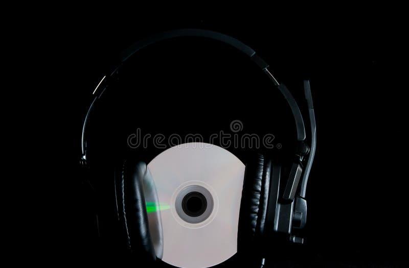 Fones de ouvido preto no disco iluminado verde do CD fotografia de stock royalty free