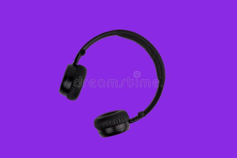 Fones de ouvido pretos isolados no fundo roxo da cor do protão na moda Conceito mínimo da música fotos de stock